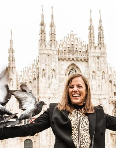 Tourist feeding pigeons in front of Duomo di Milano