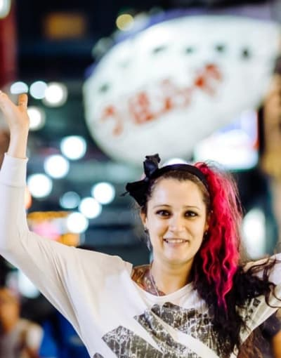 Tourist posing in front of luminous signs at night on a busy street in Osaka