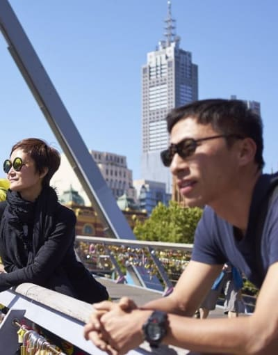 A local guide and tourists on a bridge while touring Melbourne