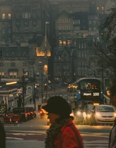 Tourists and a local guide walking along a street in Edinburgh at night