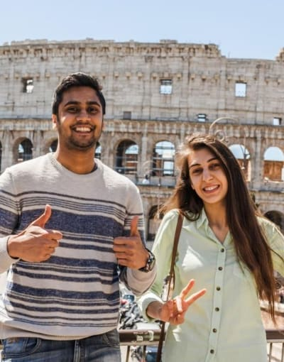 Tourist couple posing in front of the Colosseum while on a tour of Rome
