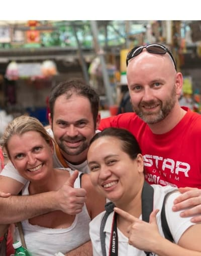 Group of tourists posing with their local guide while on a tour of the best of Bangkok