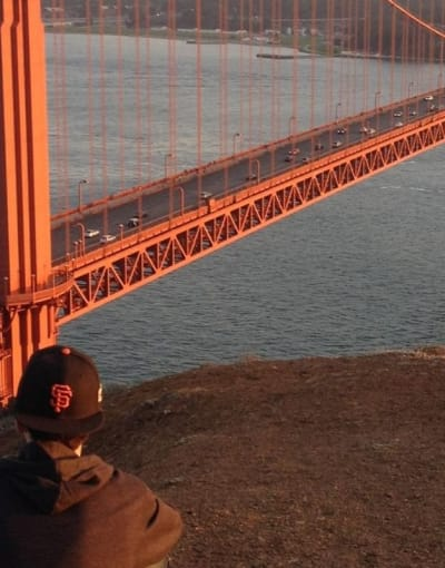 Tourist enjoying the beautiful view of Golden Gate Bridge at sunset in San Francisco
