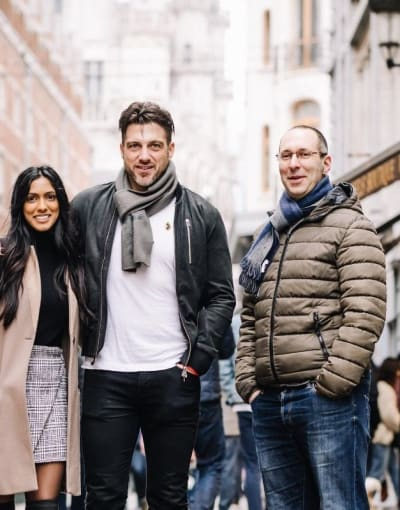 Tourists posing with a local guide on a busy street in Brussels during winter