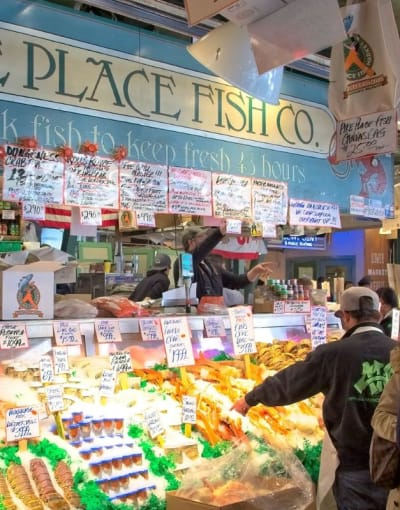 Tourists browsing the seafood options at Pike Place market in Seattle