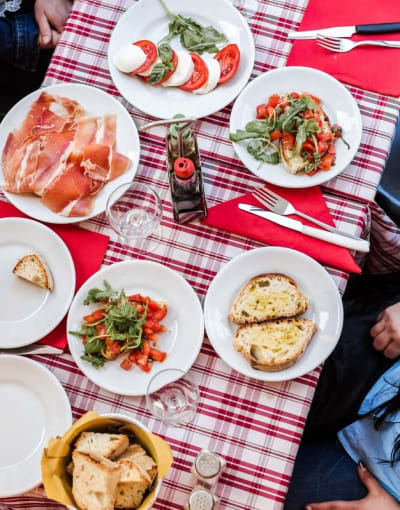 Tourist dining al fresco with a local on a food tour in Italy