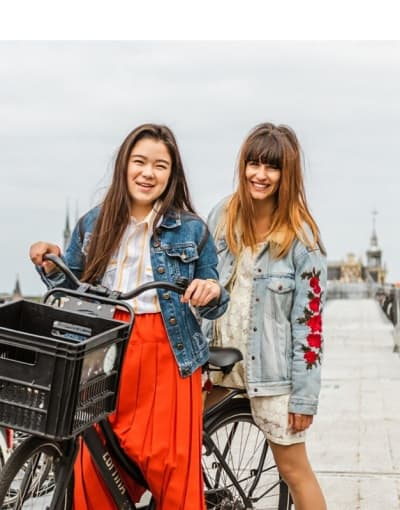 Tourists posing with their bicycle at a bicycle parking lot in Amsterdam