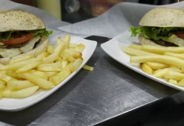 2 hamburguesas clásicas artesanales.+ papas o cascos por $20.000