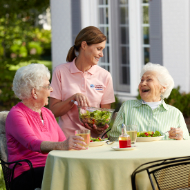 Dementia Care provider speaking with two elderly women.