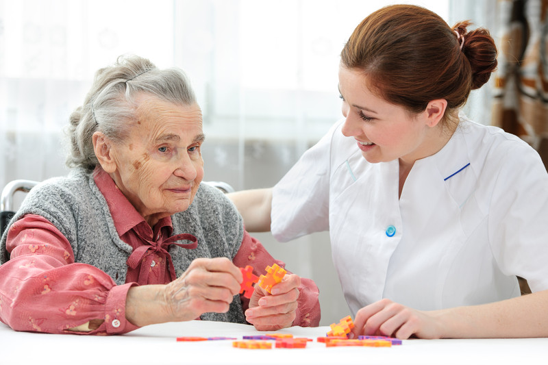 A dementia care provider helps a senior woman in Snyder, TX