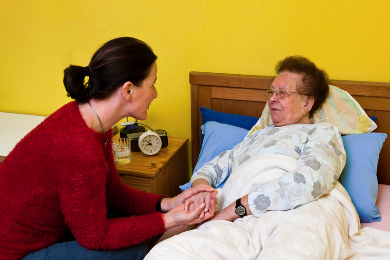A living assistance providers holds the hand of a senior woman in Snyder, TX