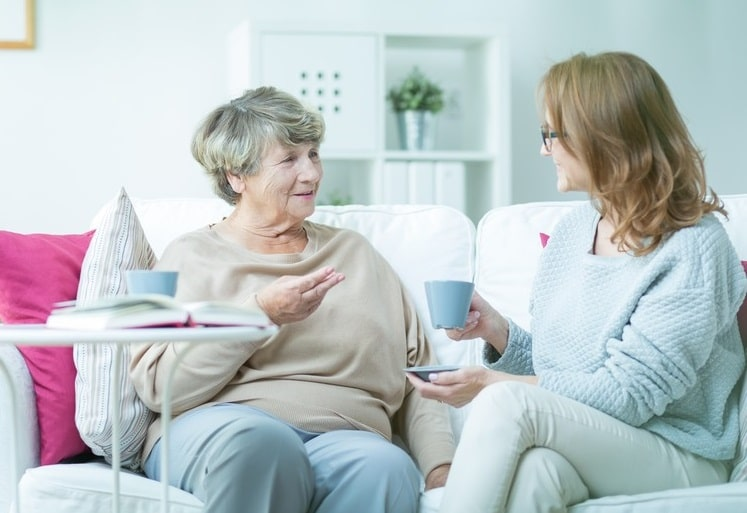 Adult home care provider and senior having coffee
