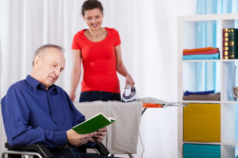 An in home care provider ironing while a senior reads in Yorktown Heights, NY