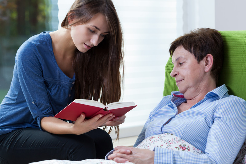 A geriatric home care provider reads to a senior woman in Kannapolis, NC