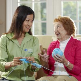 caregiver and senior inside knitting together