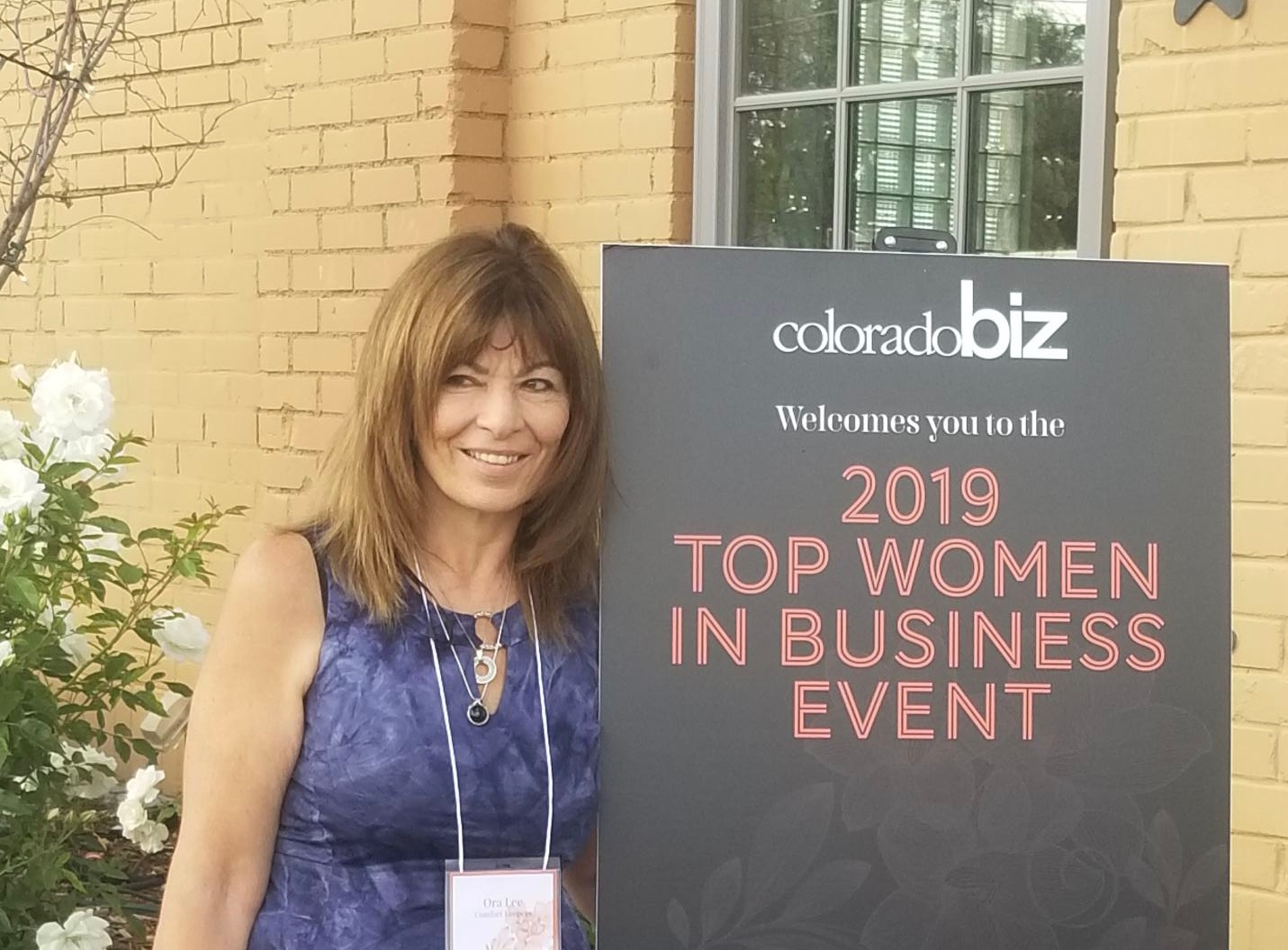 Comfort Keepers Owner standing next to a sign that says 2019 Top Women in Business Event
