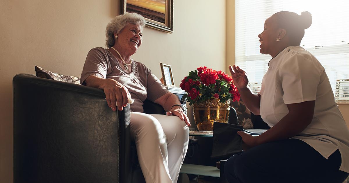 A live-in caregiver from Comfort Keepers 24-hour care service sits and talks with a senior care client.