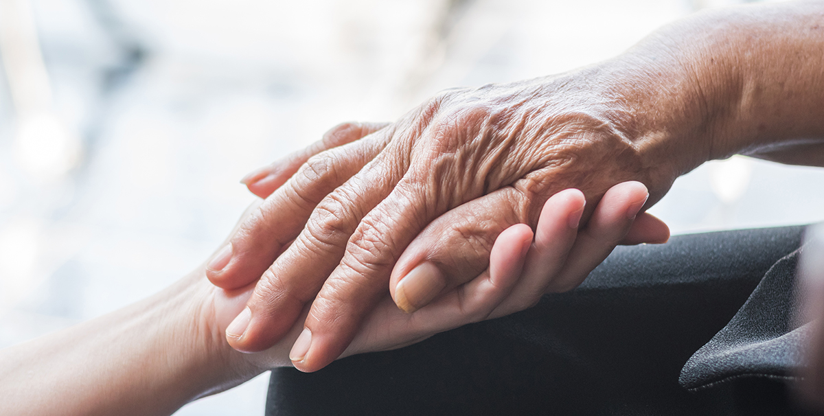 A younger hand of a Comfort Keepers in home caregiver clasps the older hand of a senior client.