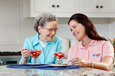 Senior eating dessert with caregiver at home.