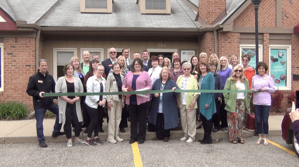 Comfort Keepers Team in Front of Their Office Building Celebrating Their 17th Anniversary