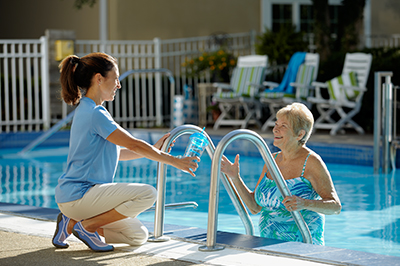 Comfort Keepers caregiver handing water bottle to senior climbing out of a pool