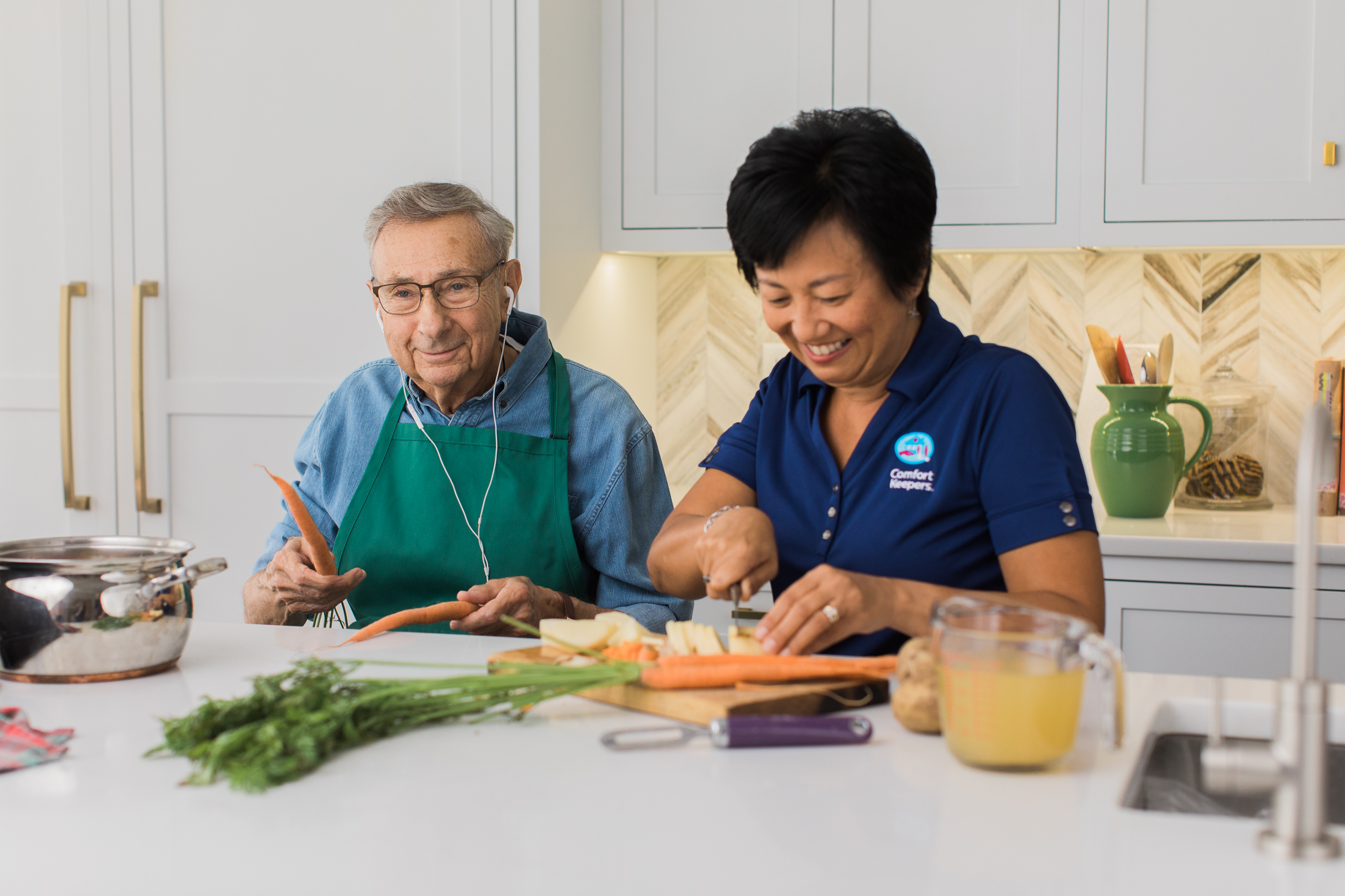 Comfort Keepers Caregiver slicing vegetables as senior listens to music and playfully drums with carrots