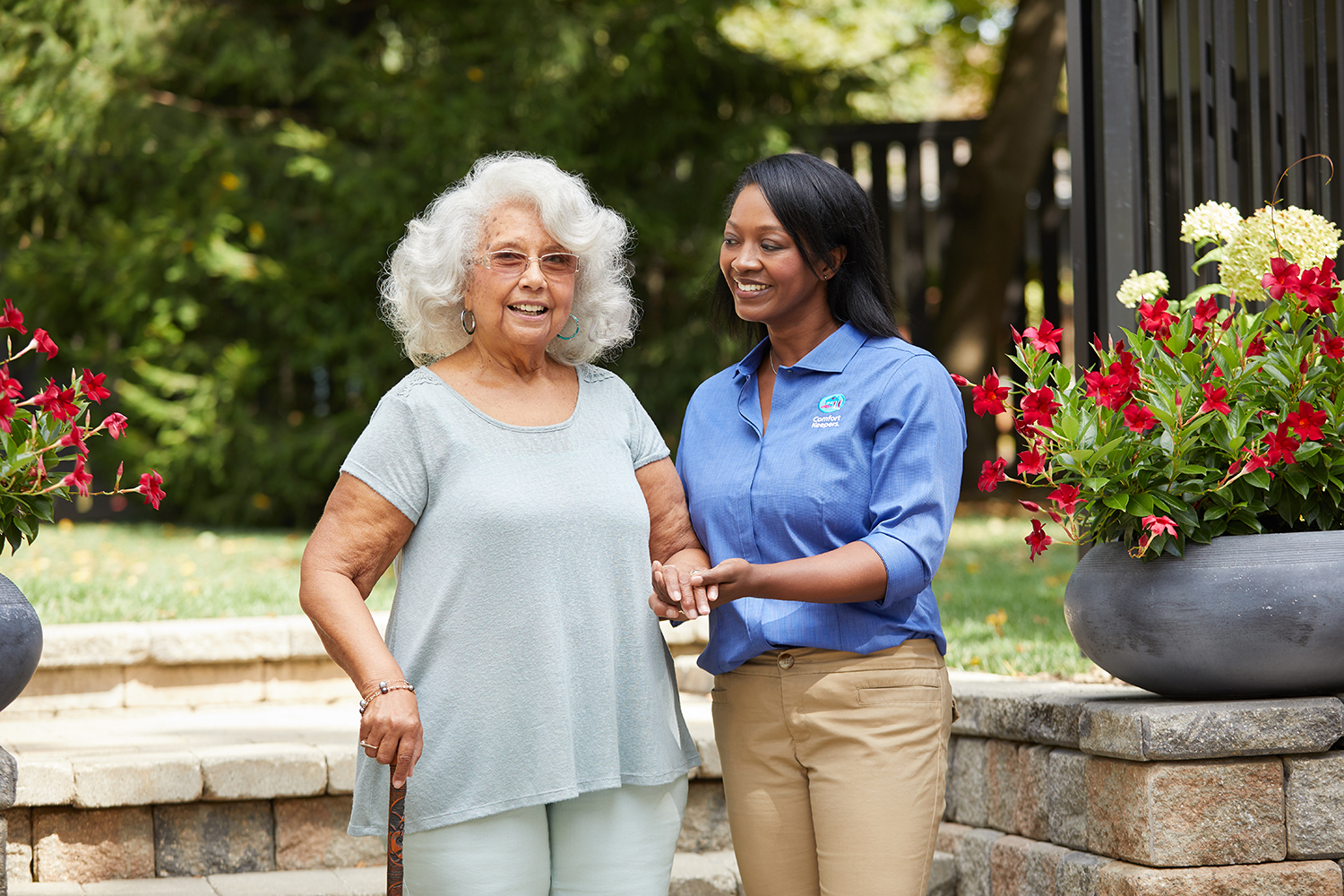 Comfort Keepers Caregiver assists senior walking with a cane