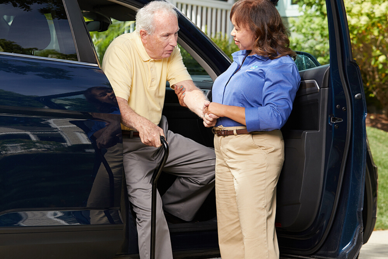 Comfort Keepers Caregiver assisting senior with cane exit van
