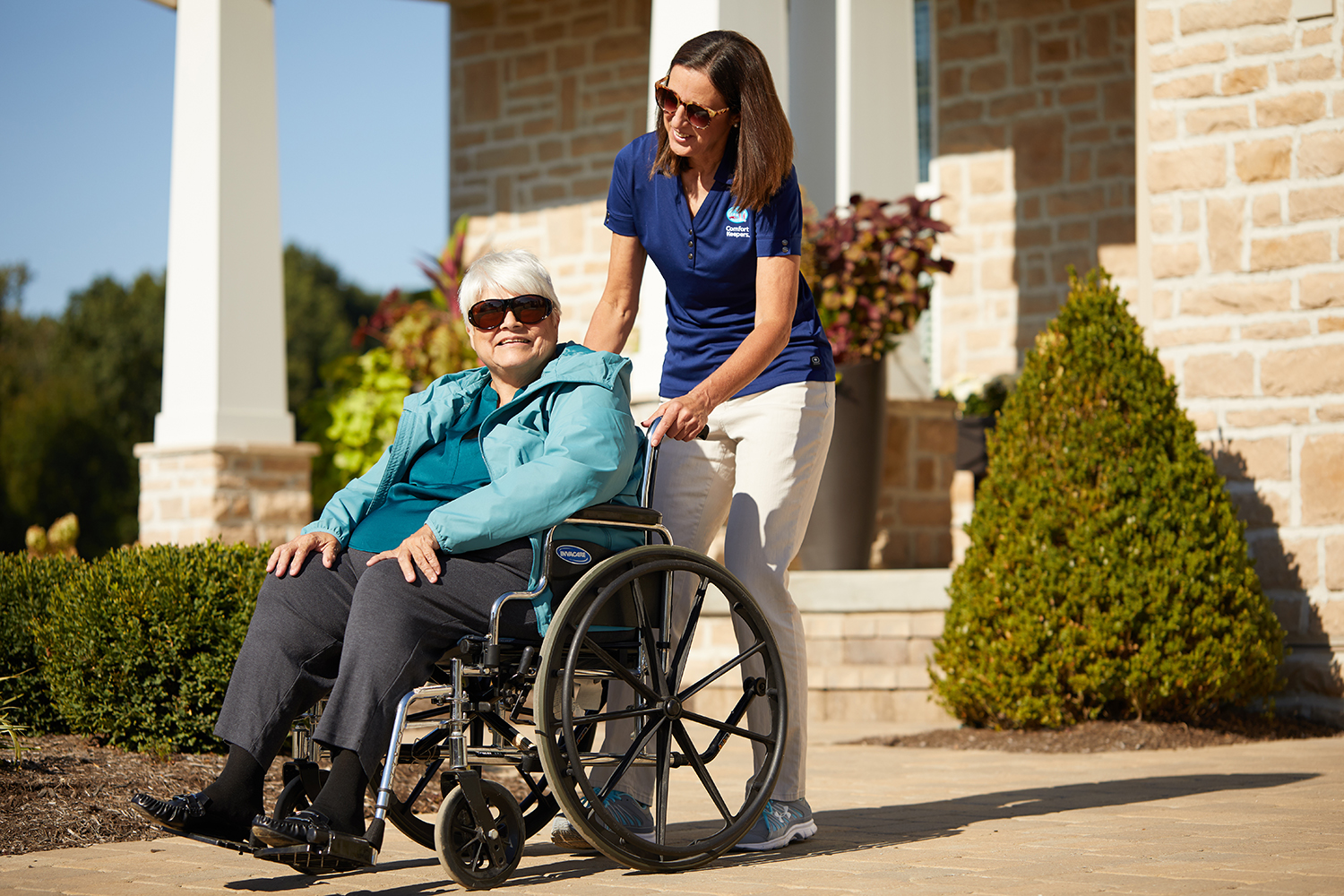 Comfort Keepers Caregiver assisting a senior in a wheelchair