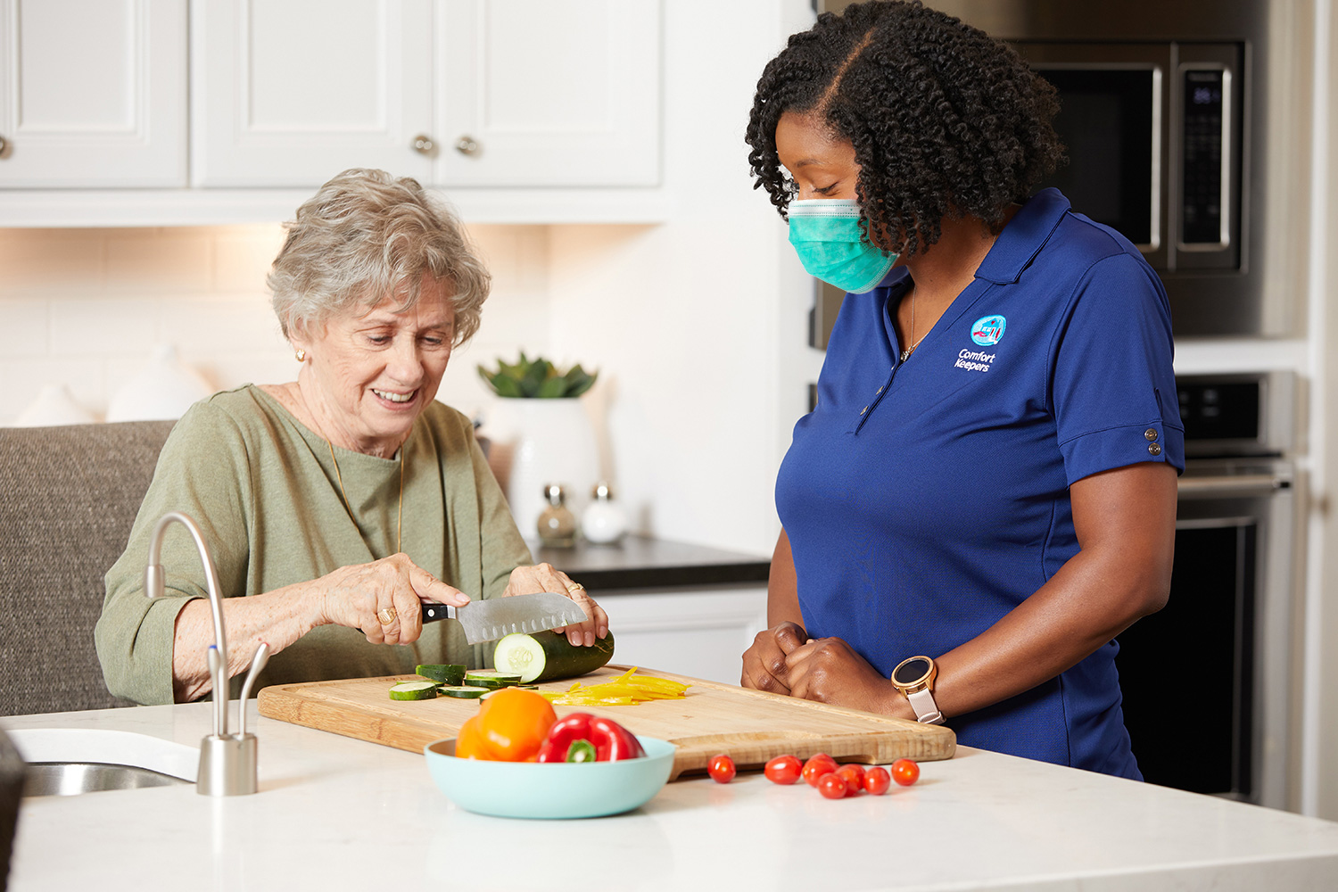 Comfort Keepers Caregiver watching senior slice a cucumber