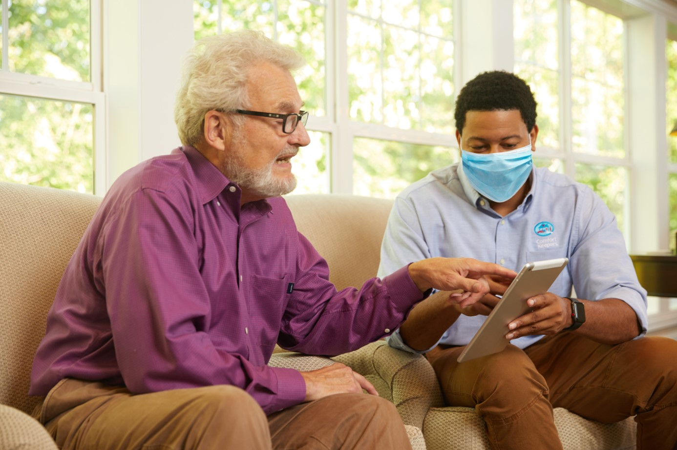 Senior and Comfort Keepers Caregiver in surgical mask touching an iPad tablet