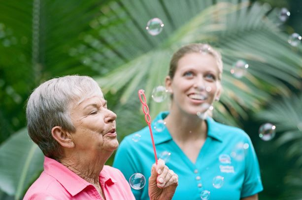 Caregiver blowing bubbles with resident as part of her companion care in Hollywood, FL