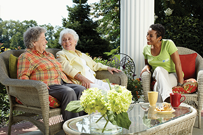 two seniors and a caregiver on patio having lunch