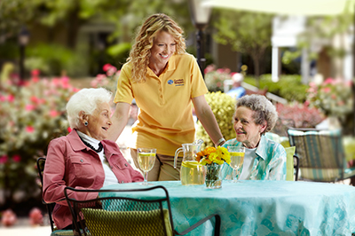 two seniors at table with caregiver in yellow shirt drinking lemonade outside oakdale