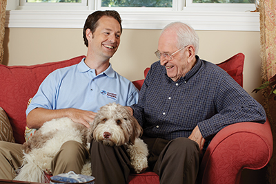 caregiver and senior on couch with dog in bayport home