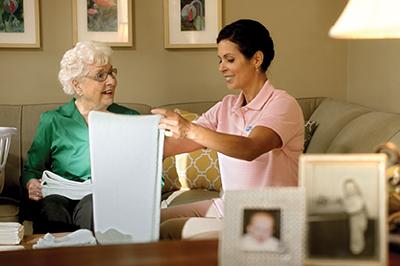 caregiver and senior folding near in senior's home near Afton, MN