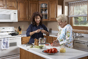 caregiver and senior in Lakeland, Mn kitchen cooking together