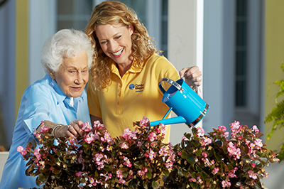 senior and caregiver watering plants outside house in Stillwater, MN