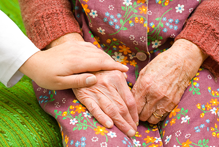 young caregiver helping and holding senior's hands