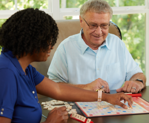 caregiver and senior playing scrabble at home