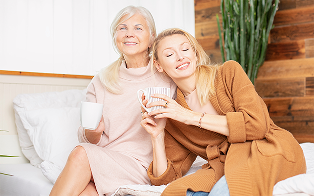Woman and her granddaughter talking and drinking coffee, sitting on bed at home.