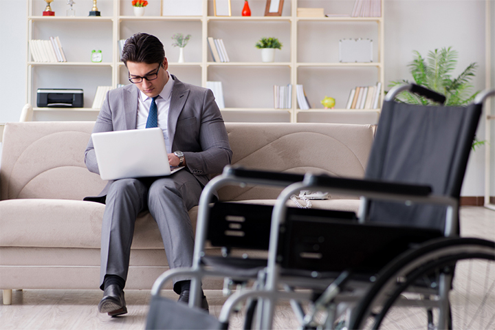 Disabled businessman on wheelchair working home