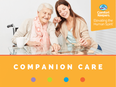 Comfort Keepers Home Care Graphic for Companion Care Services - shows a senior can caregiver playing dominos