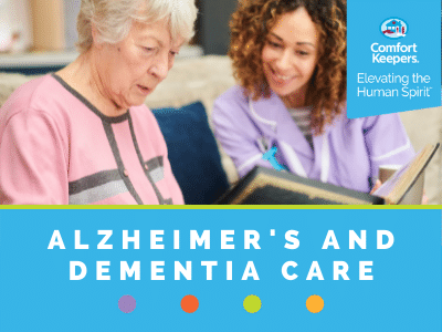 Comfort Keepers Home Care Graphic for Dementia Care - photo of senior and caregiver reading together.