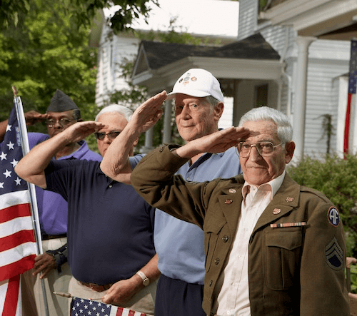 Photo of four veterans holding an American flag and saluting