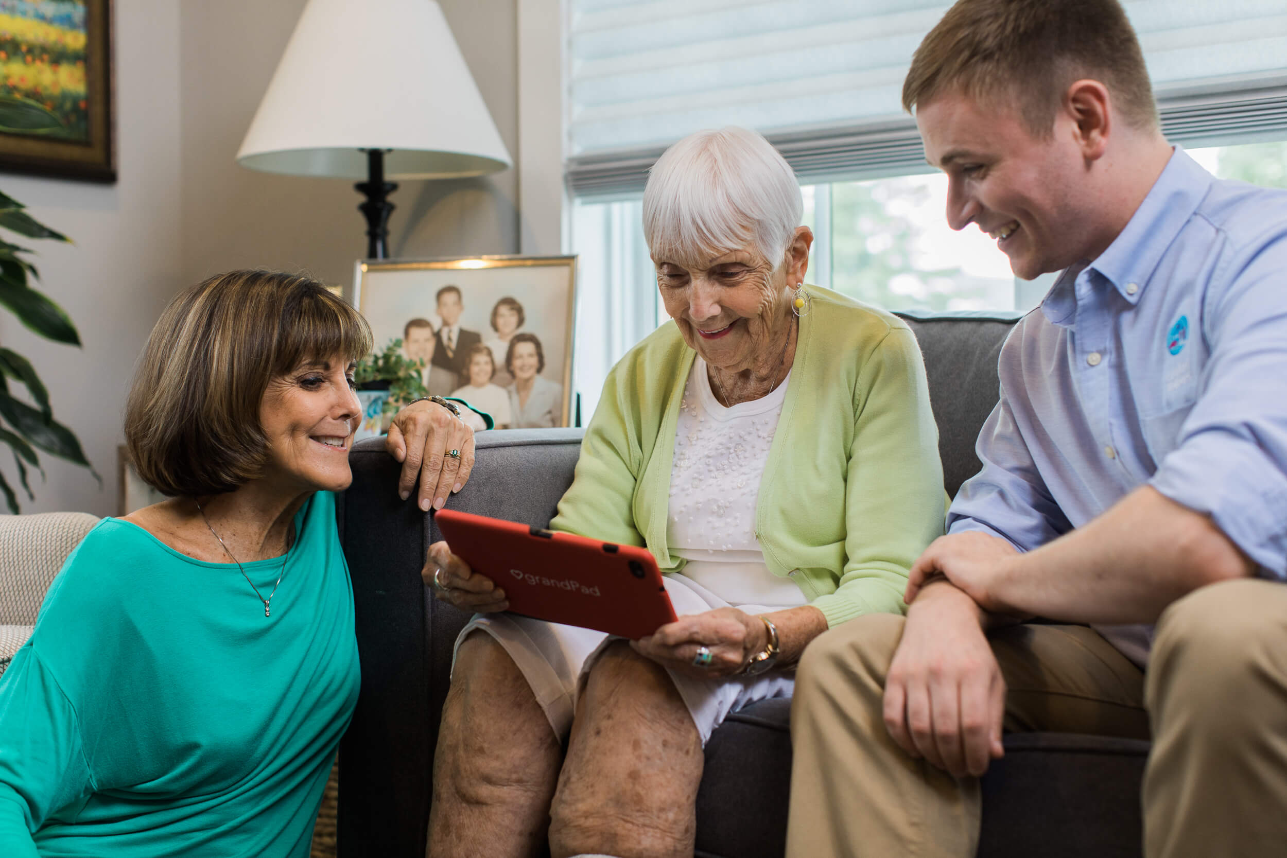 Photo of senior holding a tablet with her daughter and caregiver sitting next to her in the living room