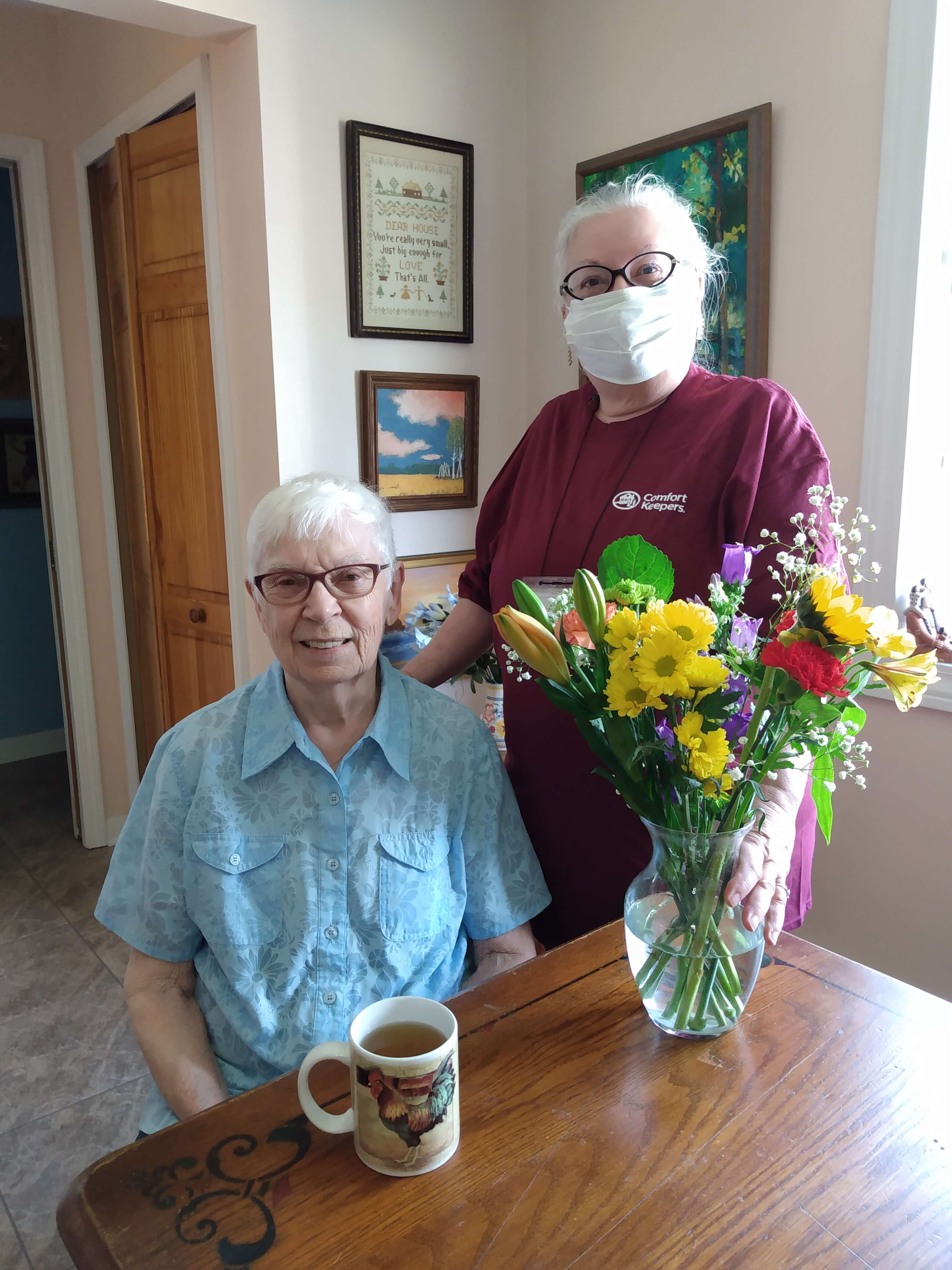 Caregiver and senior smiling for the camera next to a vase of flowers