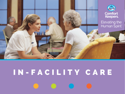 Comfort Keepers Home Care Graphic for In-Facility Care - photo of caregiver holding hands with a senior inside a nursing home.