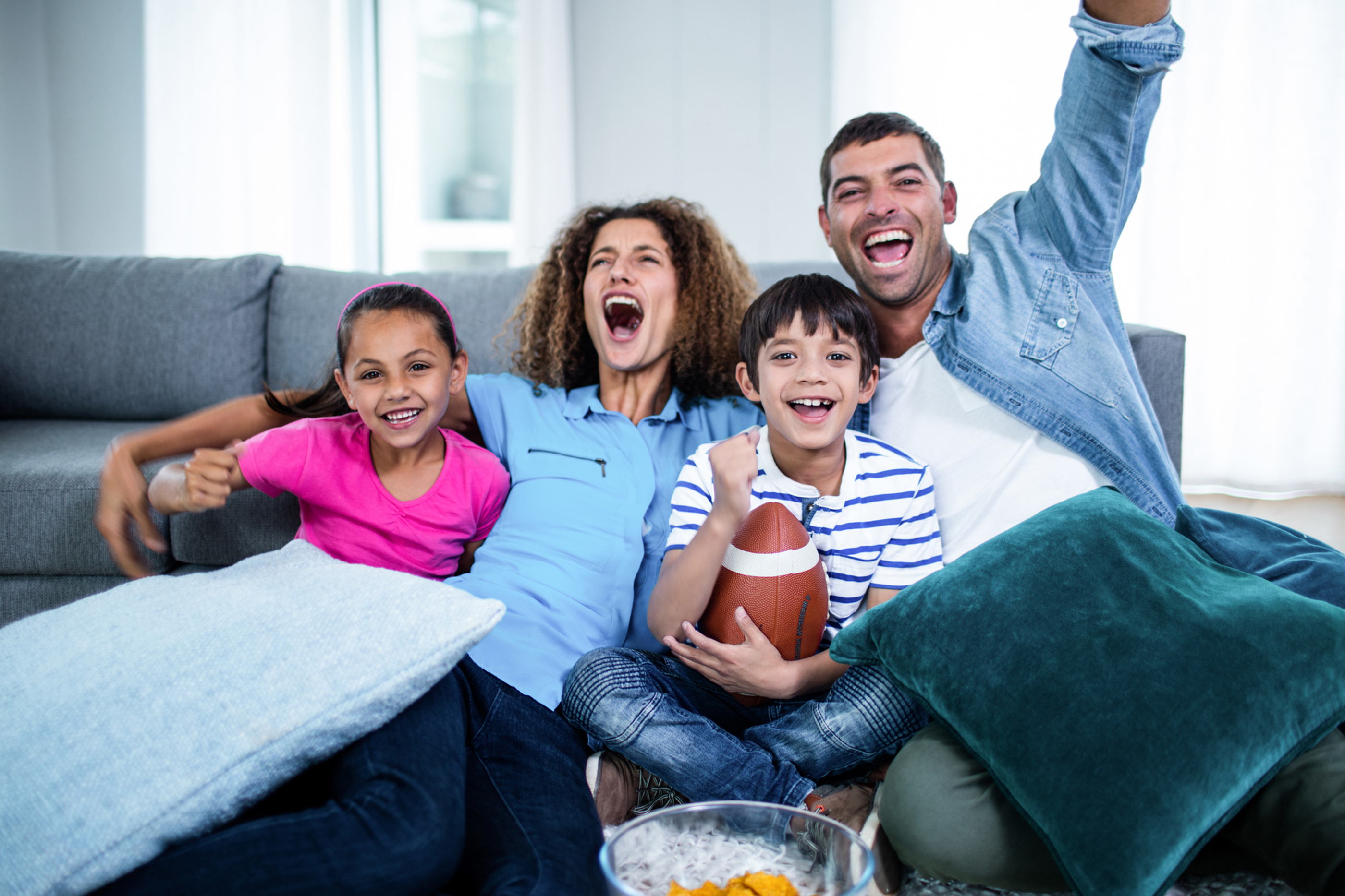 family watching sports on tv and cheering