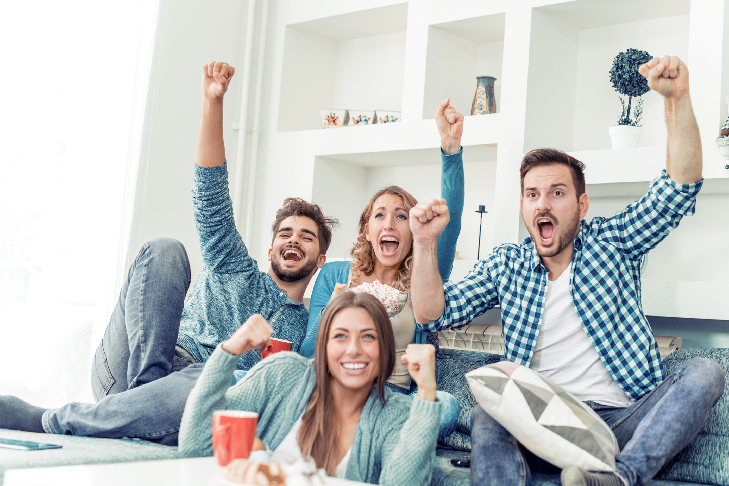friends watching sports on tv and cheering